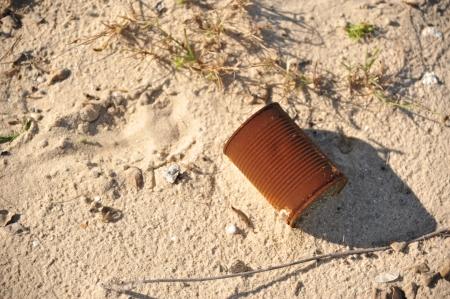 sea pollution: Rusty can trash on the beach