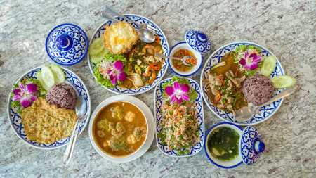 Top View Of Thai Food : Brown Rice Topped With Stir-Fried Seafood, Tuna Salad, Brown Rice Topped With Pepper Pork, Southern Sour Soup on Marble Table, Thai Cuisine