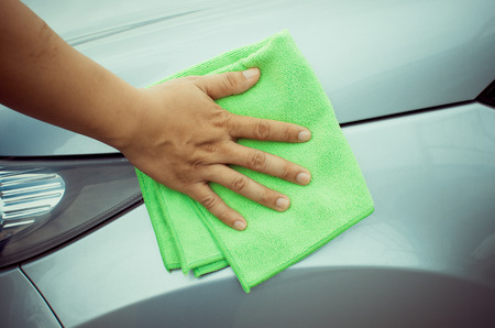 Hand with  microfiber cloth cleaning car. Stock Photo