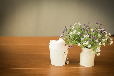 White vase of wildflowers on white wooden table and copy space