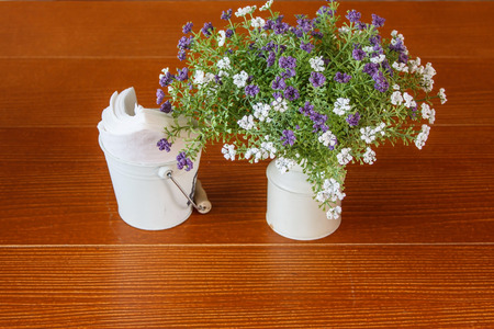 White vase of wildflowers on white wooden table with napkin