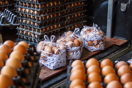 Closeup of many fresh brown eggs in carton tray, packeging egg for sale