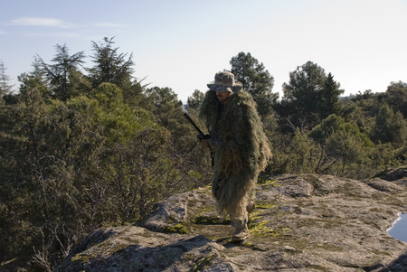 sniper training: Sniper with ghillie walking in an Airsoft party Stock Photo
