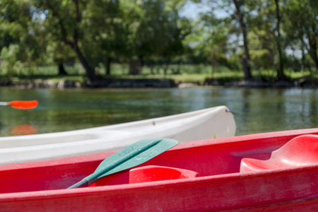 cayak: Red and White Canoe  Kayak with Green Paddle on River in Woods Stock Photo