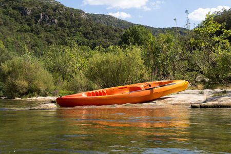 cayak: Colorful Orange Canoe or Kayak on Riverbank in Nature, Mountain Forest Background Stock Photo