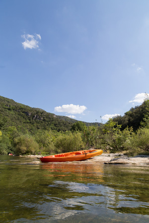cayak: Orange Canoe on River Bank in Nature with Blue Sky