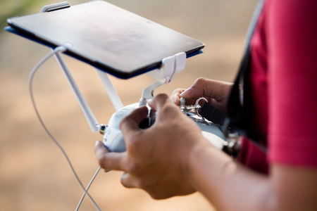 Controlling a remote helicopter drone. Stock Photo