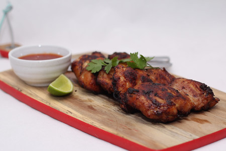chilli sauce: Grilled spicy chicken thighs with lime and sweet chilli sauce Stock Photo