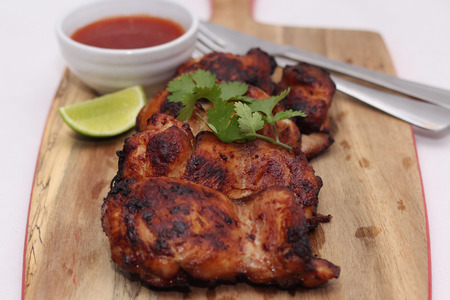 thighs: Grilled spicy chicken thighs with lime and sweet chilli sauce Stock Photo