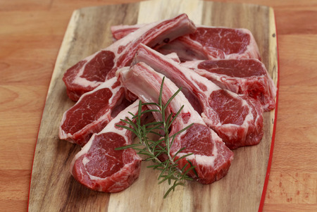 Raw lamb cutlets with rosemary on chopping board white background