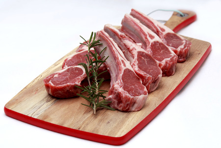 Raw lamb cutlets with rosemary on chopping board