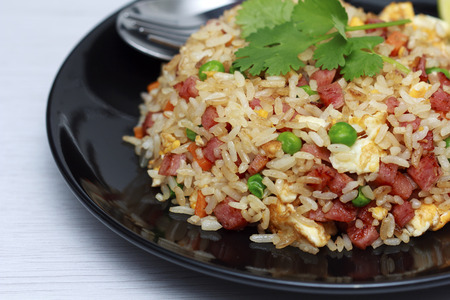Dice Bacon Fried rice in black dish with lime wedge