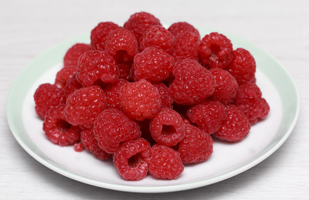 Fresh raspberries in white dish close up