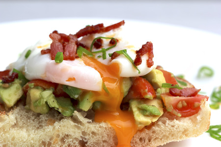 Poached eggs bacon tomatoes and avocado on toast