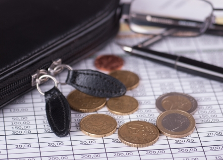 Euro coins on the background of the financial statement of lying next to the glasses and pencil case photo