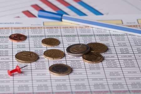common market: Euro coins and pen lying on the financial schedule