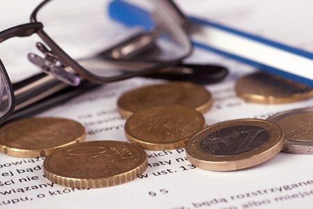 Euro coins arranged on a financial statement with glasses and pen photo