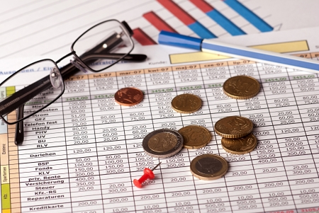 Euro coins arranged on a financial statement with glasses and pen Banco de Imagens