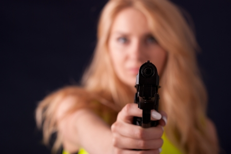 Beautiful blond woman in warning vest with a gun in her hand photo