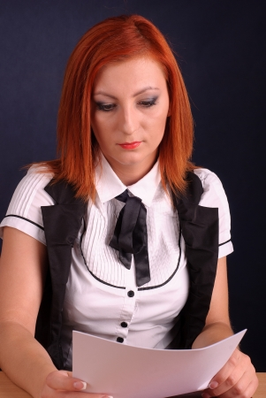 Redhead businesswoman sitting with documents photo