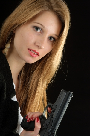 Young pretty blond woman with a handgun photo