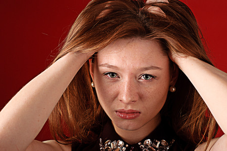 Portrait of a redhead woman having a headache on a red background photo
