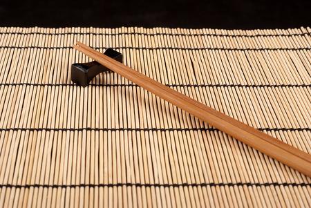Two chopsticks on a bamboo mat photo