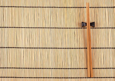 Chopsticks lying on a bamboo mat photo