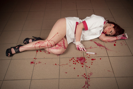 sexy nurse in a bloodstained uniform lying on the floor photo