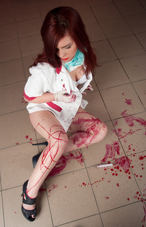 sexy nurse in a bloodstained uniform sitting on the floor photo