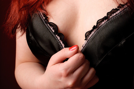 Closeup of redhead woman in black corset on red background photo