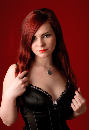Young beauty redhead woman in corset photo