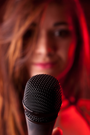 Pretty female singer on stage with microphone photo
