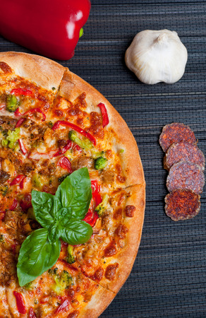 Tasty pizza with broccoli and red pepper on dark background photo