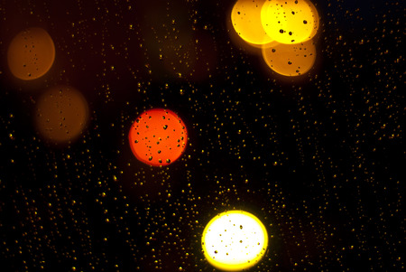 Raindrops on window at night in the city  Shallow depth of field photo