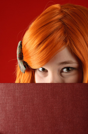 Beautiful young girl with red-orange hair with book photo