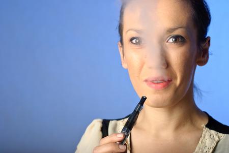 Young woman smoking e-cigarette photo
