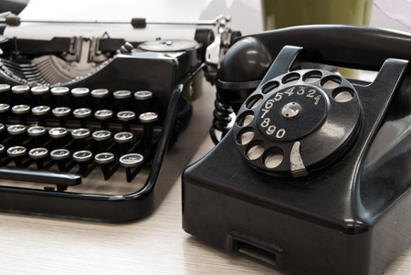 Vintage telephone and typewriter standing on the desk in the office photo