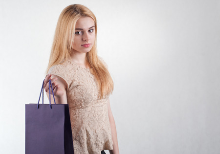 Beautiful young woman holding shopping color bag photo