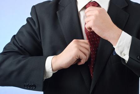 adjusting: Young businessman in suit adjusting his tie