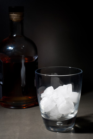 whisky glass: Whisky glass with ice cubes and bottle Stock Photo