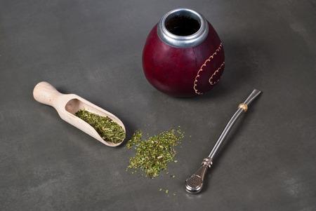yerba mate: Calabaza y bombilla con yerba mate sobre fondo gris