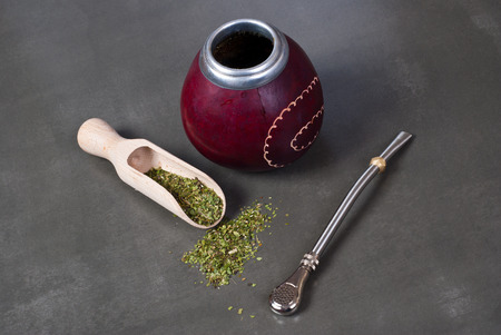 mate: Calabash and bombilla with yerba mate on gray background