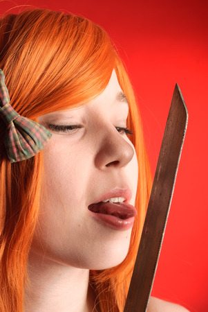 katana sword: Young beauty redhead woman licking katana sword Stock Photo