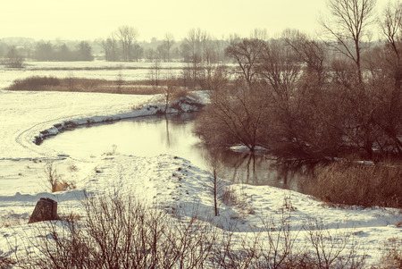 covered fields: Snow covered fields and river in winter vintage style image