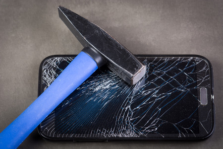 hit tech: Smartphone with broken glass and hammer on gray background Stock Photo