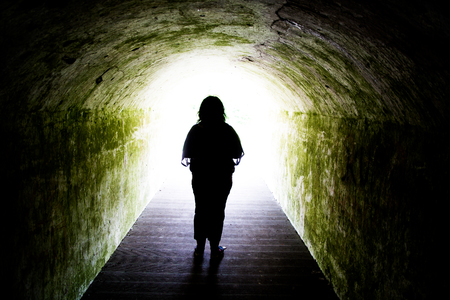 tunnel light: Silhouette of woman standing at end of tunnel -  light at end of tunnel