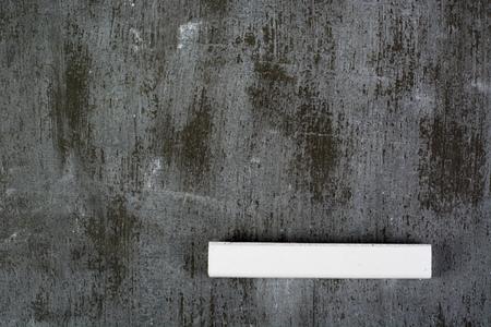 white chalk: White chalk lying on dirty old chalkboard Stock Photo