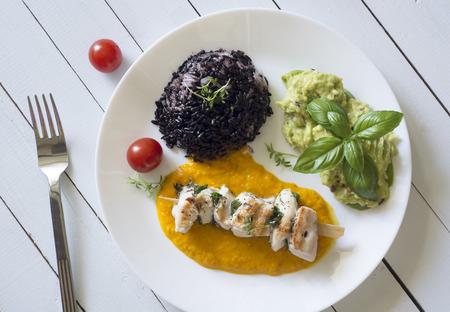Grilled shish kebab with yellow pepper sauce, red rice and guacamole - top view Stock Photo