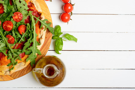 Fresh baked home made pizza with tomatoes and rocket leaves on white background